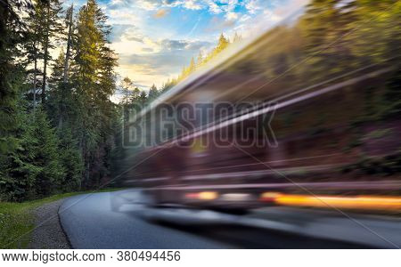 Blurred Bus In Motion Is Driving On Mountain Road In The Autumn Forest At Sunset Travel Concept