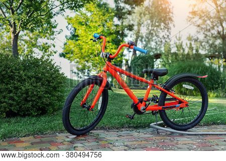 New Bright Red Color Teen Bike Stand In Garden At Home Backyard. Child Birthday Gift Present. Kid Sp