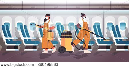 Mix Race Cleaners In Masks Disinfecting Coronavirus Cells In Airplane To Prevent Covid-19 Pandemic C