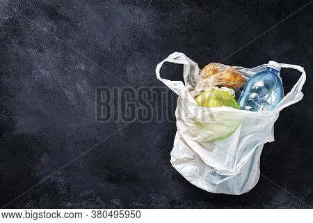 Environmental Pollution Concept Plastic Bag With Food On Dark Background Top View Copy Space