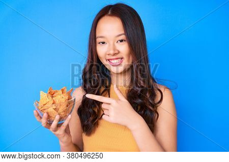 Young beautiful chinese girl holding nachos potato chips smiling happy pointing with hand and finger