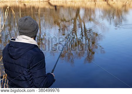 Fishing Rod In The Hands Of A Fisherman On The Lake. Fisherman With Spinning On The Background Of Wa