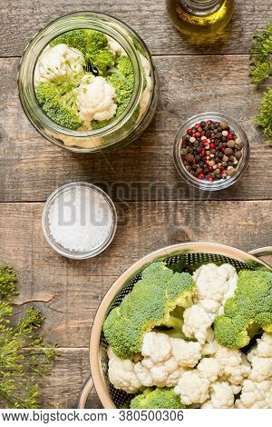Top View Jar With Canned Cauliflower And Seasonings On Wooden Kitchen Table. Food Preservation And C