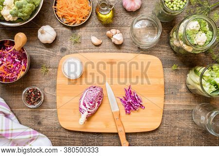 Top View Jars With Canned Vegetables, Raw Ingredient And Seasonings On Wooden Kitchen Table. Food Pr