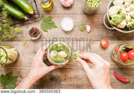 Hand Adds Canning Ingredients To The Jar And Other Canning Vegetables On Wooden Background. Food Pre