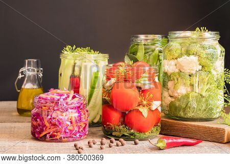 Jars With Canned Vegetables On Wooden Kitchen Table. Food Preservation And Conservation Concept