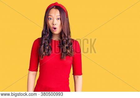 Young beautiful chinese girl wearing casual clothes and diadem scared and amazed with open mouth for surprise, disbelief face