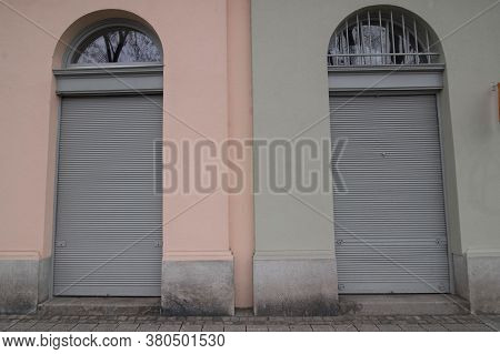Lowered Roller Shutter At Two Shop Entrances, Closed Business In Economic Crisis