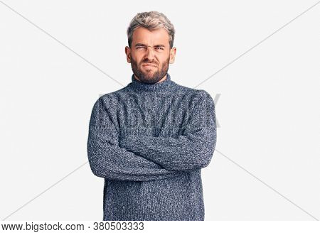 Young handsome blond man wearing casual sweater skeptic and nervous, disapproving expression on face with crossed arms. negative person.