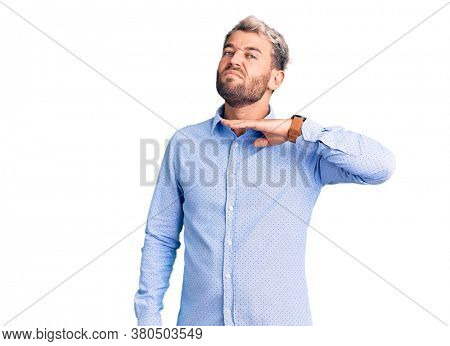 Young handsome blond man wearing elegant shirt cutting throat with hand as knife, threaten aggression with furious violence
