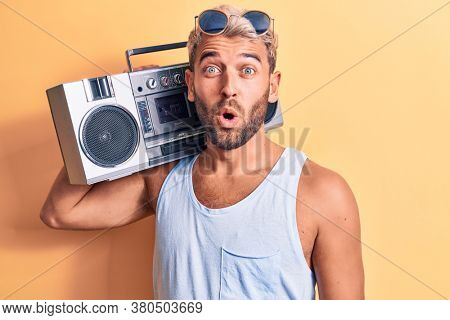 Young handsome blond man with beard wearing sunglasses listening to music using boombox scared and amazed with open mouth for surprise, disbelief face