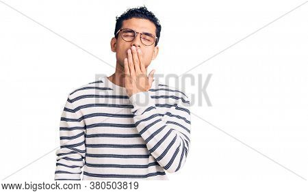 Hispanic handsome young man wearing casual clothes and glasses bored yawning tired covering mouth with hand. restless and sleepiness.