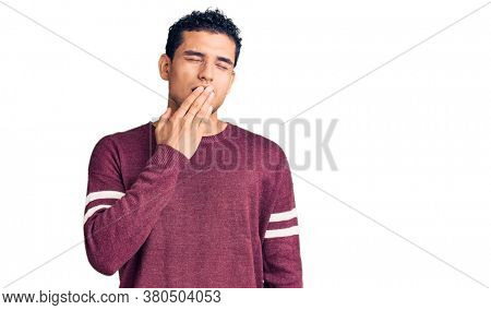 Hispanic handsome young man wearing casual clothes bored yawning tired covering mouth with hand. restless and sleepiness.