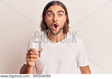 Young handsome man drinking glass of water scared and amazed with open mouth for surprise, disbelief face