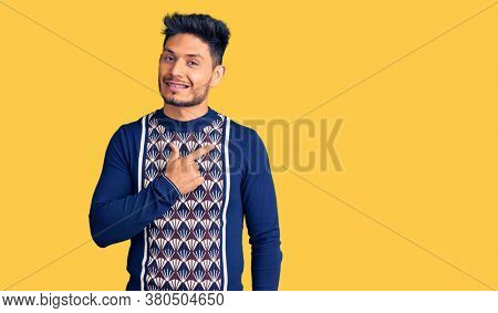 Handsome latin american young man wearing casual winter sweater cheerful with a smile of face pointing with hand and finger up to the side with happy and natural expression on face