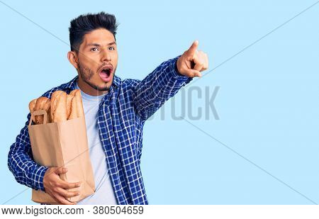Handsome latin american young man holding paper bag with bread pointing with finger surprised ahead, open mouth amazed expression, something on the front