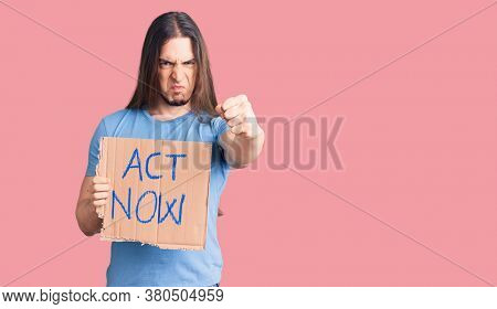 Young adult man with long hair holding act now banner annoyed and frustrated shouting with anger, yelling crazy with anger and hand raised