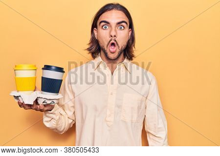 Young handsome man holding coffee to takeaway scared and amazed with open mouth for surprise, disbelief face