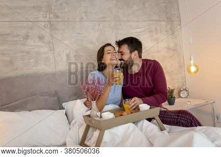Beautiful Young Couple In Love Wearing Pajamas Sitting In Bed, Man Surprising Woman By Bringing Her