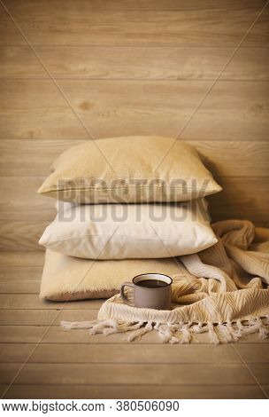 Cozy Background With Pillows And Cup Of Beverage Against Blurred Wooden Wall As Symbol Of Warmth And