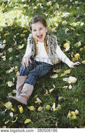 Happy Little Girl At Autumn Park Wearing Waistcoat. Childhood, Happiness And Season Concept