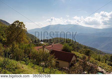 Little Farm House With Farmstead On Th Slops. Far Mountains And White Clouds Background. Montenegro.