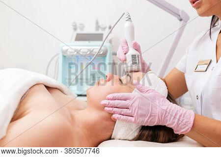 A Cosmetologist In Rubber Gloves Does The Rf-lifting Procedure On The Face. In The Background, The R