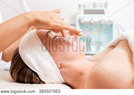 Cosmetologist Makes A Woman A Procedure Of Facial Acupressure. Side View. Cosmetic Equipment In The