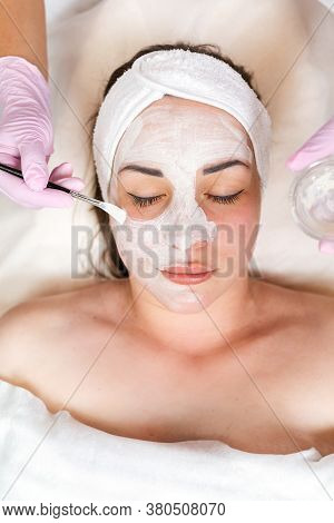 The Cosmetologist In Medical Gloves Holds A Bowl With Cosmetics, Applying A Brush Mask On The Client