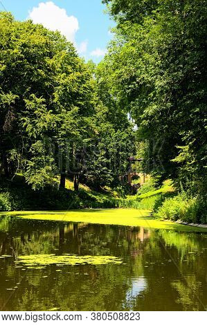 Gorgeous Summer Nature Landscape. Picturesque Pond With Lily Pads On The Surface And Old Brick Bridg
