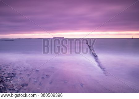 Warm Vibrant Pink Purple Sunset Over The Breakwater In Water Of Ocean And Sea. Concept Of Beautiful