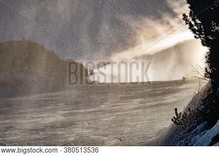 Snow Canon Works On Slope. Winter Mountain Landscape With Rime And Snow Covered Spruce Trees