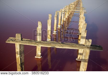 Salt Strip Fenced With Dried Wooden Pillars On The Lake With Pink Salt. Salt Production.