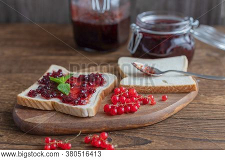 Homemade Red Currant Jam In A Glass Jar And A Number Of Berries On A Wooden Background. Toast Or Bre