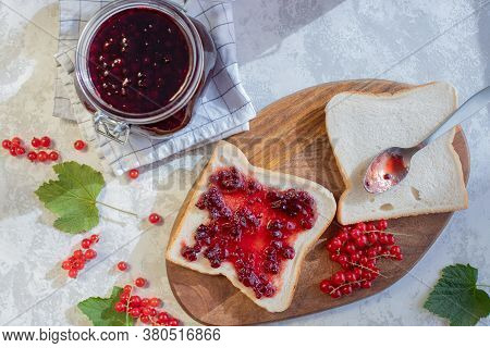 Top View Of A Sandwich With Homemade Jam Or Red Currant Jam On A Wooden Board In Bright Sunlight And