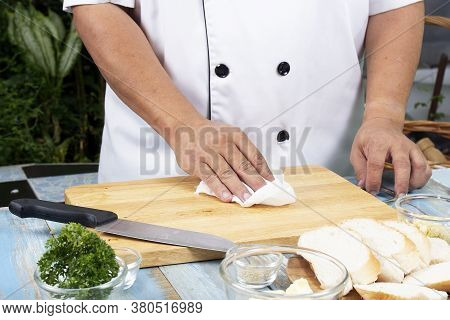 Chef Cleaning Wooden Broad With Tissue Paper / Cooking Garlic Bread Concept