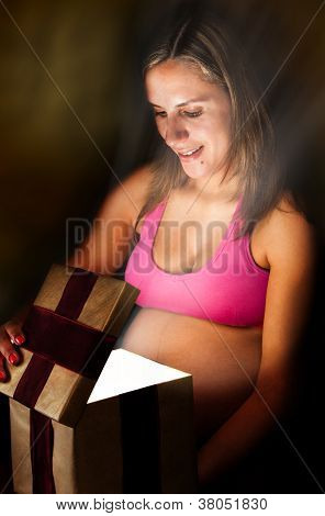 Pregnant Woman Opening a Gift Box With a Christmas Present