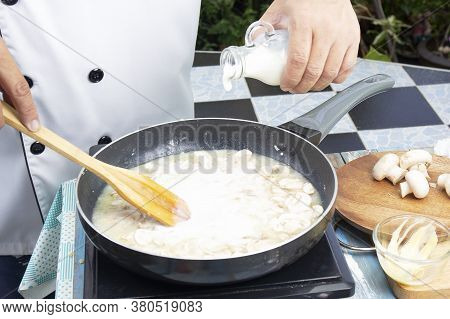 Chef Pouring Fresh Milk The Pan For Cooking Mushroom Cream Soup / Cooking Mushroom Cream Soup Concep