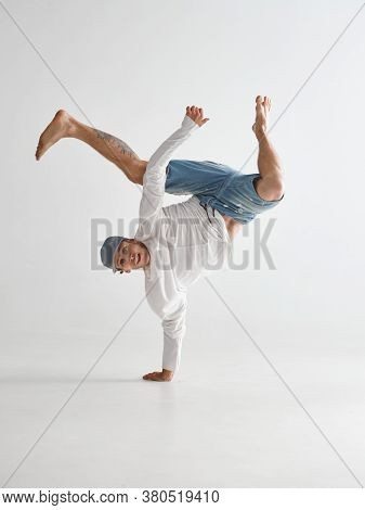 Young Breakdancer Stands On One Arm Dancing Hip-hop Isolated On White Background. Break Dance School
