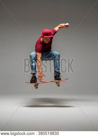 Cool Young Guy Skateboarder Levitates On Skateboard In Studio On Grey Background. Photography About
