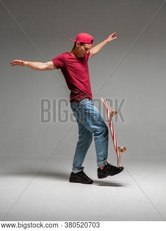 Cool Guy Skateboarder Keeps Skateboard On Leg In Studio On Grey Background. Photography About Skateb