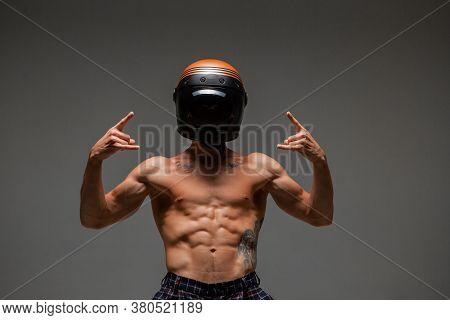 Athletic Guy Racer In Helmet With Naked Torso And Goat Gestures Stands In Studio. Kart Racing Poster
