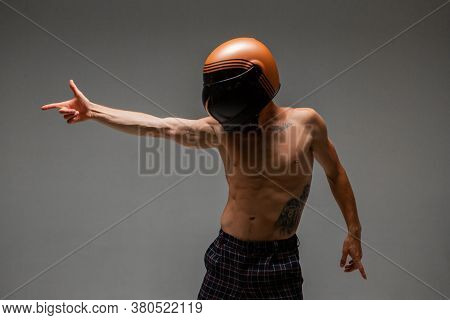 Athletic Guy Racer In Helmet With Naked Torso And Pointing Gesture Stand In Studio. Kart Racing Post