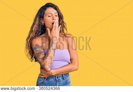 Young hispanic woman with tattoo wearing casual clothes bored yawning tired covering mouth with hand. restless and sleepiness.