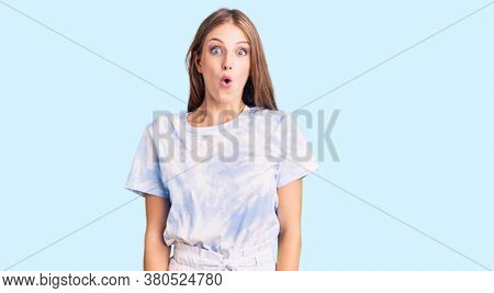 Young beautiful blonde woman wearing tye die tshirt scared and amazed with open mouth for surprise, disbelief face