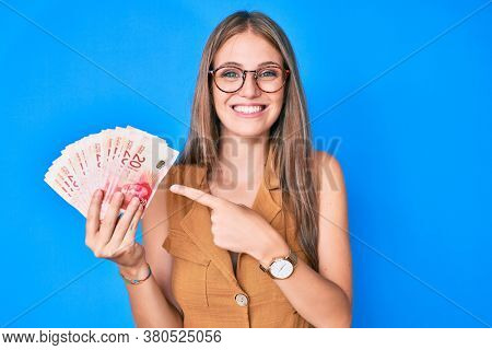Young blonde girl holding israeli shekels smiling happy pointing with hand and finger