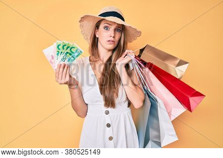 Young blonde girl holding shopping bags and israeli shekels clueless and confused expression. doubt concept.