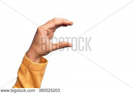 Hand of caucasian young man showing fingers over isolated white background picking and taking invisible thing, holding object with fingers showing space