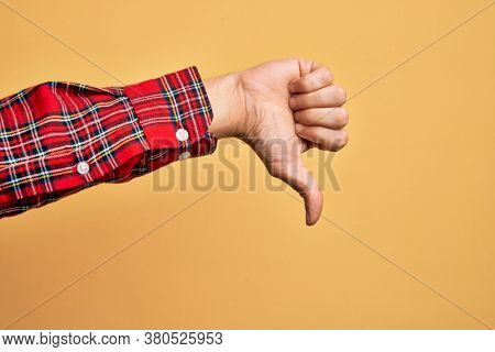 Hand of caucasian young man showing fingers over isolated yellow background doing thumbs down rejection gesture, disapproval dislike and negative sign