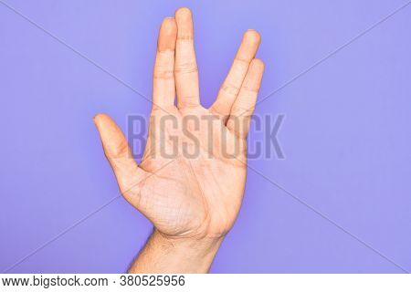 Hand of caucasian young man showing fingers over isolated purple background greeting doing Vulcan salute, showing hand palm and fingers, freak culture